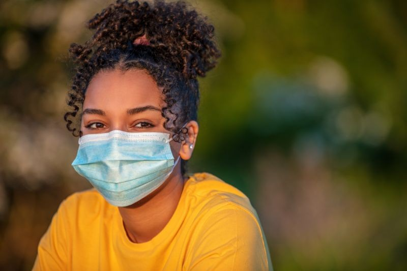 Young African-American girl wearing face mask outside